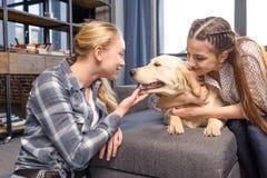 Dos muchachas que abrazan el perro del golden retriever en el sofá en casa Imagen de archivo