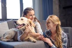 Dos muchachas que abrazan el perro del golden retriever en el sofá en casa Imagen de archivo libre de regalías