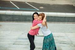 Dos muchachas que abrazan en la calle Fotografía de archivo libre de regalías