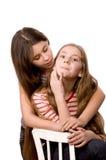 Dos muchachas que abrazan las manos en blanco Imágenes de archivo libres de regalías