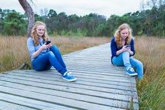 Dos muchachas que actúan los teléfonos móviles que se sientan en la trayectoria en naturaleza Imágenes de archivo libres de regalías