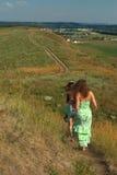 Dos muchachas que caminan abajo de la colina Fotografía de archivo
