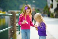 Dos muchachas que caminan abajo de las calles de la ciudad de la orilla del lago de Hallstatt en las montañas austríacas por la t Foto de archivo libre de regalías