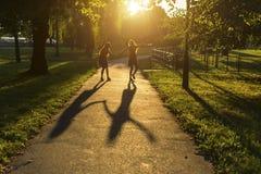 Dos muchachas que caminan abajo del callejón que lleva a cabo las manos, durante puesta del sol asombrosa Fotografía de archivo