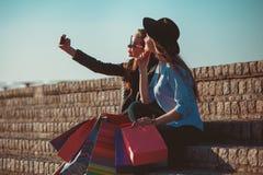 Dos muchachas que caminan con compras en las calles de la ciudad Fotos de archivo