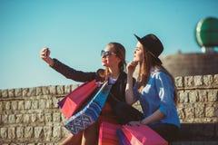 Dos muchachas que caminan con compras en las calles de la ciudad Foto de archivo