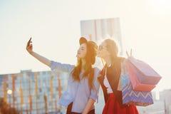 Dos muchachas que caminan con compras en las calles de la ciudad Imagenes de archivo