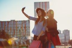 Dos muchachas que caminan con compras en las calles de la ciudad Imagen de archivo libre de regalías