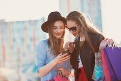 Dos muchachas que caminan con compras en las calles de la ciudad Fotografía de archivo libre de regalías