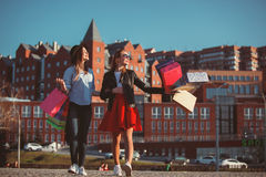 Dos muchachas que caminan con compras en las calles de la ciudad Imagen de archivo