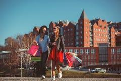 Dos muchachas que caminan con compras en las calles de la ciudad Imágenes de archivo libres de regalías