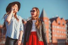 Dos muchachas que caminan con compras en las calles de la ciudad Fotografía de archivo