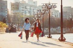 Dos muchachas que caminan con compras en las calles de la ciudad Foto de archivo libre de regalías