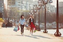 Dos muchachas que caminan con compras en las calles de la ciudad Fotos de archivo libres de regalías