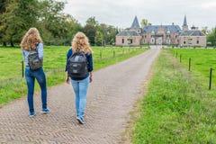 Dos muchachas que caminan en el camino que lleva para escudarse Imagen de archivo libre de regalías