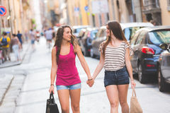 Dos muchachas que caminan en la calle que lleva a cabo las manos Imagen de archivo libre de regalías