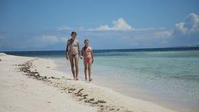 Dos muchachas que caminan en una playa tropical almacen de video
