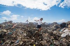 Dos muchachas que caminan entre basura en la descarga de basura Foto de archivo libre de regalías