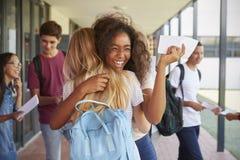 Dos muchachas que celebran resultados del examen en pasillo de la escuela Imágenes de archivo libres de regalías