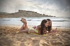 Dos muchachas que charlan en la playa Foto de archivo