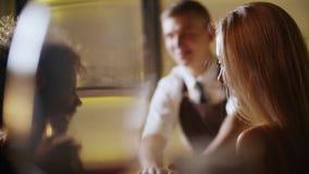 Dos muchachas que charlan y que beben el vino en la barra de lujo En el fondo el camarero hace los cócteles almacen de metraje de vídeo