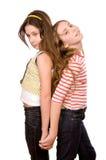 Dos muchachas que colocan y que abrazan las manos Foto de archivo