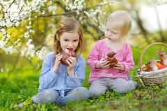 Dos muchachas que comen conejitos del chocolate en Pascua Foto de archivo libre de regalías