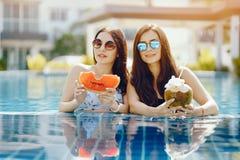 Dos muchachas que comen fruta por la piscina imagen de archivo
