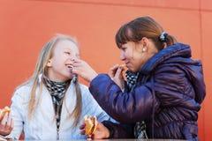 Dos muchachas que comen las hamburguesas Imagen de archivo