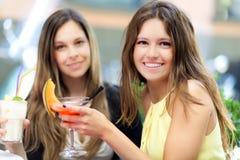 Dos muchachas que comen un aperitivo al aire libre Fotografía de archivo
