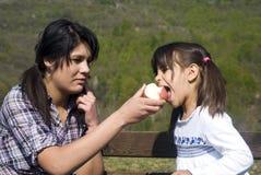 Dos muchachas que comen una manzana Imágenes de archivo libres de regalías