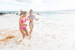 Dos muchachas que corren en la playa del océano Imágenes de archivo libres de regalías