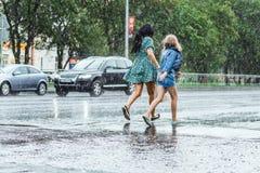 Dos muchachas que corren lejos en la calle durante las fuertes lluvias imágenes de archivo libres de regalías