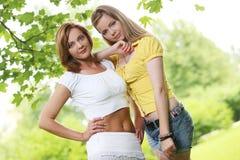 Dos muchachas que cuelgan hacia fuera en parque Imágenes de archivo libres de regalías
