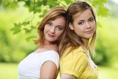 Dos muchachas que cuelgan hacia fuera en parque Fotos de archivo libres de regalías