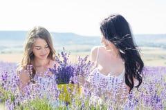 Dos muchachas que descansan sobre el campo de la lavanda Fotos de archivo
