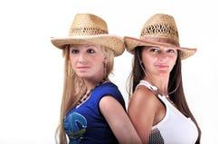 Dos muchachas que desgastan los sombreros y la sonrisa de vaquero Fotos de archivo