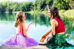 Dos muchachas que dicen las colas de hadas en el lago fotos de archivo libres de regalías