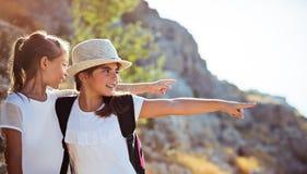 Dos muchachas que disfrutan de excursión a las montañas fotos de archivo libres de regalías