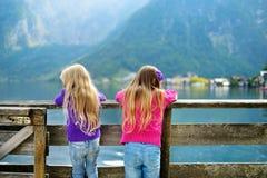 Dos muchachas que disfrutan de la vista escénica de la ciudad de la orilla del lago de Hallstatt en las montañas austríacas por l Imágenes de archivo libres de regalías