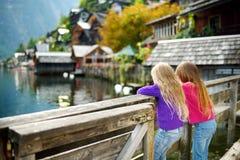 Dos muchachas que disfrutan de la vista escénica de la ciudad de la orilla del lago de Hallstatt en las montañas austríacas por l Imagen de archivo