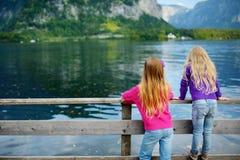 Dos muchachas que disfrutan de la vista escénica de la ciudad de la orilla del lago de Hallstatt en las montañas austríacas por l Foto de archivo libre de regalías