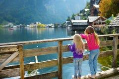 Dos muchachas que disfrutan de la vista escénica de la ciudad de la orilla del lago de Hallstatt en las montañas austríacas por l Fotos de archivo