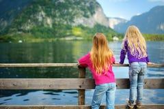 Dos muchachas que disfrutan de la vista escénica de la ciudad de la orilla del lago de Hallstatt en las montañas austríacas por l Imagen de archivo libre de regalías