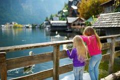Dos muchachas que disfrutan de la vista escénica de la ciudad de la orilla del lago de Hallstatt en las montañas austríacas por l Fotos de archivo libres de regalías