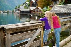 Dos muchachas que disfrutan de la vista escénica de la ciudad de la orilla del lago de Hallstatt en las montañas austríacas por l Fotografía de archivo