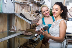 Dos muchachas que eligen los zapatos en la tienda Imagen de archivo libre de regalías