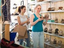 Dos muchachas que eligen los zapatos en la tienda Imágenes de archivo libres de regalías