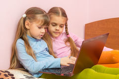 Dos muchachas que empujan pregunta de la búsqueda en un teclado del ordenador portátil Fotografía de archivo