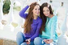 Dos muchachas que escuchan la música en sus smartphones Fotografía de archivo
